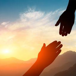 Duas mãos indo de encontro a outra com um por do sol ao fundo