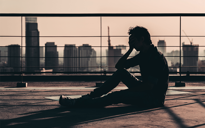Pessoa sentada no terraço de um prédio com a mão na cabeça e expressão de desanimo