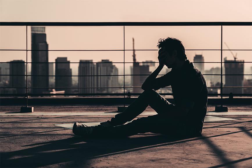 Uma pessoa sentada no terraço de um prédio com a mão na cabeça e expressão de desanimo