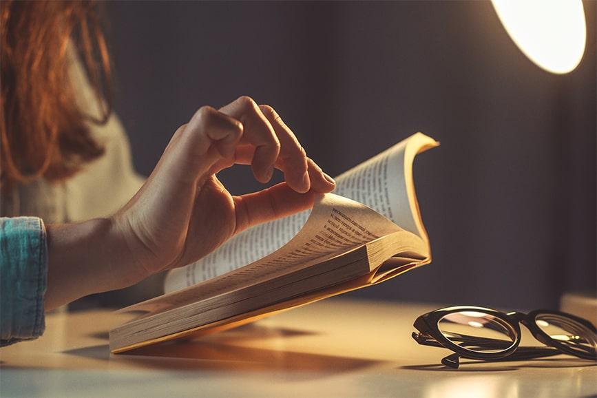 Pessoa lendo um livro e virando a página.